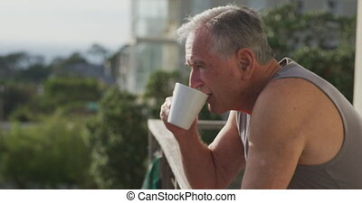 Senior man drinking coffee on terrace - Side view close up ...