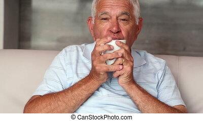 Senior man drinking cofffee on couc