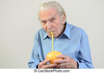 Senior man drinking fresh grapefruit juice