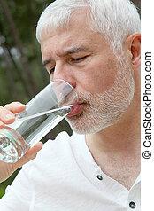 Senior man drinking fresh water