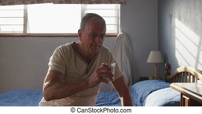 Senior man drinking water at home