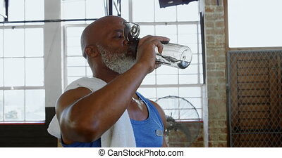 Senior man drinking water in the fitness studio 4k -...