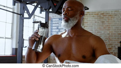 Senior man drinking water in the fitness studio 4k