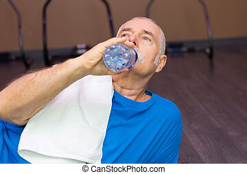 senior man drinking water in the gym