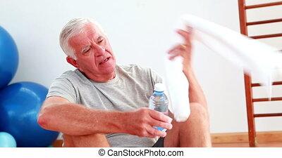 Senior man drinking water sitting o