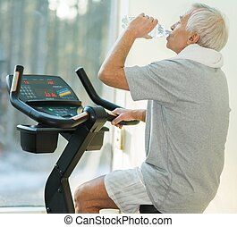 Senior man drinking while doing exercise on a bike in a fitness club