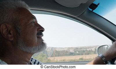Senior Man Drives A Car In Summer Day, Man Enjoys Driving