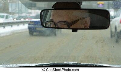 Senior man driving a car in winter