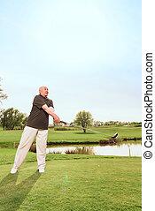 Senior man driving ball towards on course