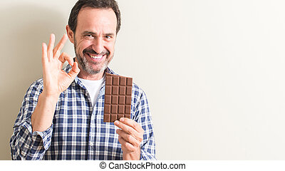 Senior man eating chocolate bar doing ok sign with fingers, excellent symbol