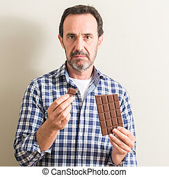 Senior man eating chocolate bar with a confident expression on smart face thinking serious