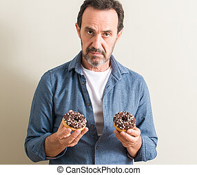 Senior man eating chocolate donut with a confident expression on smart face thinking serious