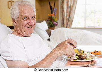 Senior Man Eating Hospital Food In Bad