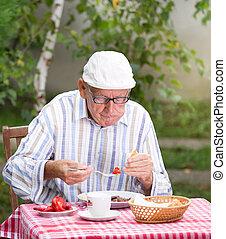 Senior man eating in garden