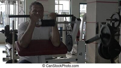 Senior man exercising on bicep training machine