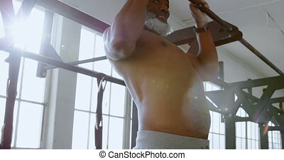 Senior man exercising pull up on a pull up bar in the...
