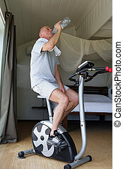 Senior man exercising with a bottle of water