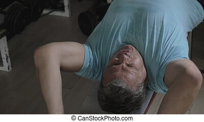 Senior man exercising with disk weight