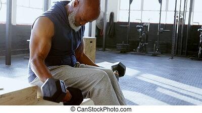 Senior man exercising with dumbbell in the fitness studio 4k...