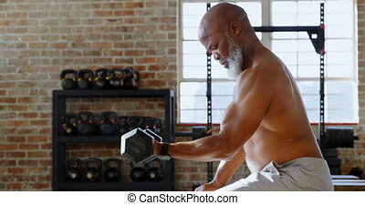 Senior man exercising with dumbbells in the fitness studio 4k