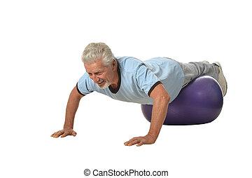 Senior man exercising with fitness ball