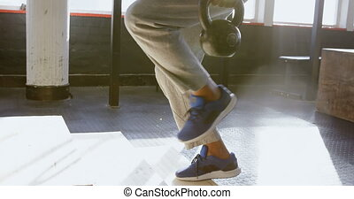 Senior man exercising with kettle bell in the fitness studio...