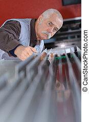 senior man factory employee at work