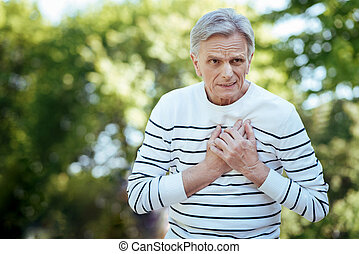 Senior man feeling awful pain in chest on the street