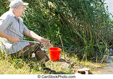 Senior man fishing on a freshwater lake