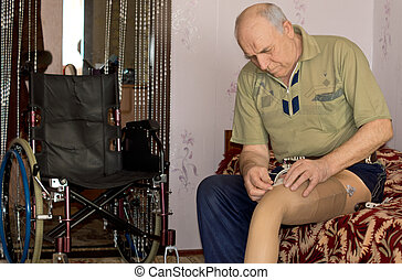 Senior man fitting his prosthetic leg to his stump following...