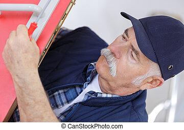 senior man fixing the door
