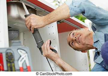senior man fixing the sink in kitchen