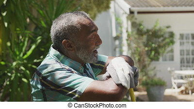 Side view of a senior African American having a good time in a garden, leaning on a shovel, looking at camera, on a sunny day, in slow motion