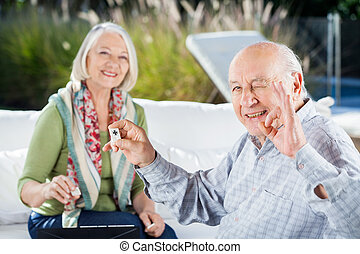 Senior Man Gesturing Okay While Playing Rummy With Woman - ...