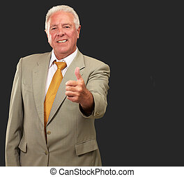 Senior Man Gesturing On Black Background