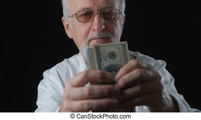 Senior man gets money. He counts dollar bills. Salary...