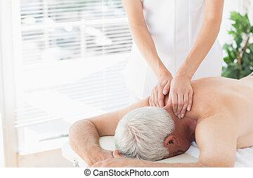 Senior man getting back massage in medical office