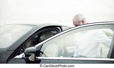 Senior man getting in car, rainy weather. Slow motion.