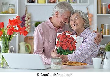 Senior man gives  woman a gift