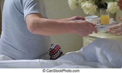 Senior man giving breakfast tray to wife in bed