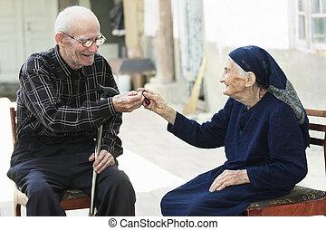 Senior man giving cherry to woman