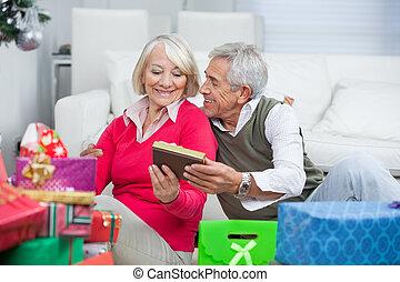 Senior Man Giving Christmas Gift To Woman