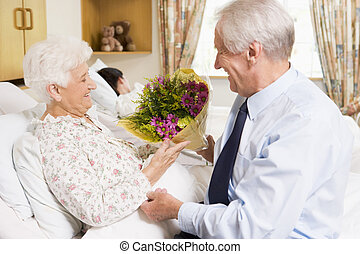 Senior Man Giving Flowers To His Wife In Hospital