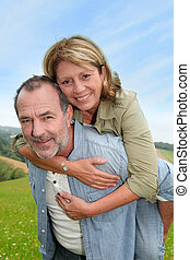Senior man giving piggyback ride to wife
