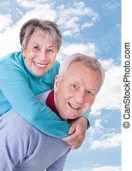 Senior Man Giving Piggyback Ride To Woman Against Sky