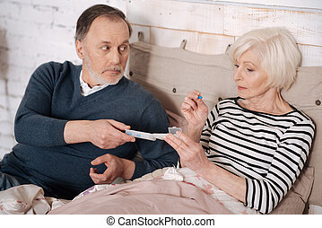 Senior man giving pills to his wife