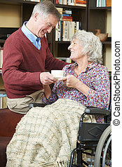 Senior Man Giving Wife In Wheelchair Cup Of Tea
