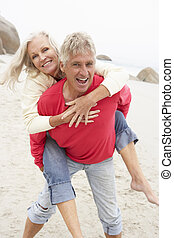Senior Man Giving Woman Piggyback On Winter Beach