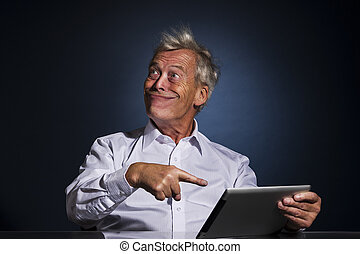 Senior man grinning and pointing to his tablet - Senior ...