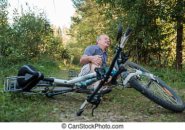 Senior man has a pain after he fell from his bike. He can...